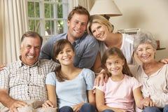 Multi Generations-Familien-Gruppe, die auf Sofa Indoors sitzt Stockbilder