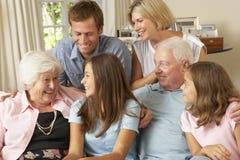 Multi Generations-Familien-Gruppe, die auf Sofa Indoors sitzt Stockfotos