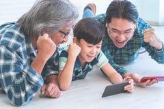 Multi Generationsfamilie, die Erfolg unter Verwendung der beweglichen Internet-Technologie hat lizenzfreie stockbilder