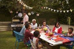 Multi Generationsschwarzfamilie, die einen Grill am 4. Juli hat lizenzfreie stockfotos
