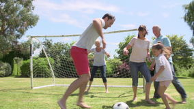 Multi generazione che gioca a calcio nel giardino insieme stock footage