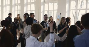 Multi gente di affari etnica felice del gruppo che balla insieme celebrando le feste all'ufficio leggero moderno, partito del pos video d archivio