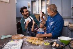 Multi-geração feliz que dá a elevação cinco na cozinha imagem de stock royalty free