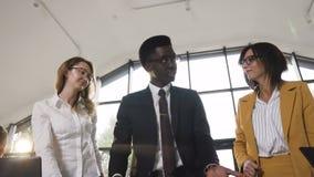 Multi giovane gruppo creativo etnico di partenza che ha una riunione di progresso che esamina i dati stampati e che analizza i gr archivi video