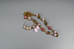 Multi grânulos e bracelete da cor com encantos em um fundo cinzento Fotografia de Stock
