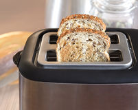 Multi-grain bread in toaster. Roasted multi-grain bread popping up from toaster machine Stock Photography