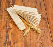 Multi-grain crispbread and wheat ears on wooden surface Royalty Free Stock Images