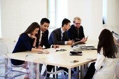 Multi grupo étnico de executivos seguros que falam entre se ao esperar o começo da conferência imagens de stock