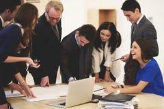 Multi grupo étnico novo de coordenadores inteligentes que reveem modelos durante a reunião no interior moderno do escritório imagem de stock