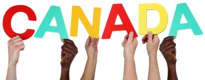 Multi grupo de pessoas étnico que guarda a palavra Canadá imagens de stock royalty free
