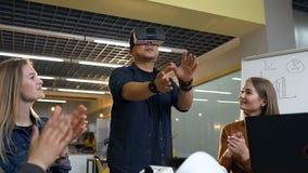 Multi gruppo etnico di affari che applaude al giovane uomo giapponese facendo uso dei vetri di realtà virtuale per il riuscito af video d archivio