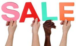 Multi gruppo etnico di gente che tiene la vendita di parola immagine stock