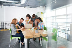 Multi gruppo etnico di riuscita gente di affari creativa che per mezzo di un computer portatile nel corso della riunione schietta Immagine Stock