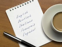 Multi-languages. List in a notebook with a pen and a cup of coffee on a wooden background Royalty Free Stock Photos