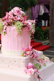 Multi layered wedding cake. Fancy layered wedding cake decorated with flowers. Grand piano on the background Stock Photography