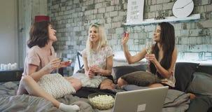Multi le signore etniche felici e carismatiche a casa su un letto moderno hanno il tempo divertente, il champagne bevente e cibo  stock footage
