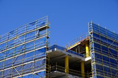 Scaffolding and Blue Safety Cladding on Construction. A multi level building under construction with scaffolding and blue nylon safety cladding, and a clear blue stock photo