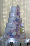 Multi level white wedding cake with pink flowers. Stock Images