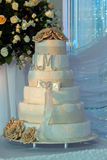 Multi level white wedding cake on a silver base and gold flowers Royalty Free Stock Image