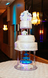 multi level white wedding cake on a silver base and pink flowers on top Stock Photos