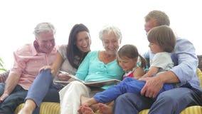 Multi libro di lettura della famiglia della generazione insieme stock footage