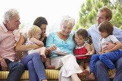 Multi livro de leitura da família da geração no jardim Seat Fotografia de Stock