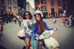 Multi meninas étnicas em um 'trotinette' na cidade europeia foto de stock