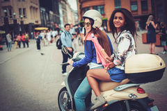 Multi meninas étnicas em um 'trotinette' na cidade europeia imagem de stock