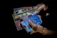 Multi moedas nacionais em uma mão de uma pessoa imagens de stock