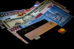 Multi moedas nacionais junto com Revolut MasterCard e cartão da passagem da prioridade para o acesso da sala de estar do aeroport imagem de stock