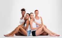 Multi mulheres étnicas que sentam-se no assoalho fotografia de stock royalty free