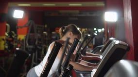 Multi povos étnicos que mantêm o ajuste exercitar no equipamento moderno do gym Ostenta mulheres bonitas no gym O jogo do instrut filme