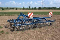 A multi-purpose harrow for aerating fields, spreading straw, cultivating stubble and fighting weeds. A multi-purpose, farm tractor pulled harrow for aerating Stock Images