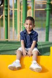 Multi-racial boy at the park. Cute multi-racial boy at the park sitting and smiling royalty free stock images