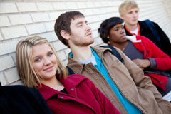 Multi-racial college students against a brick wall. Multi-racial college students outside against a brick wall royalty free stock photo