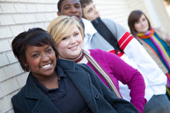 Multi-racial college students against a brick wall. Multi-racial college students outside against a brick wall stock photo