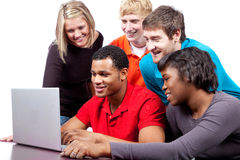Multi-racial college students by a computer. A group of multi-racial college students sitting around a computer royalty free stock image
