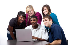 Multi-racial college students sitting by computer. A group of multi-racial college students sitting around a computer royalty free stock photo