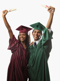 Multi racial couple in cap and gown Stock Photos