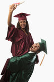 Multi racial couple in cap and gown Stock Photography