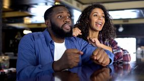 Multi-racial couple rooting for national team watching game, entertainment. Stock photo stock image