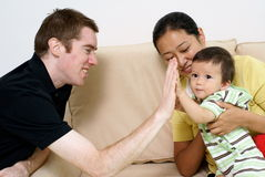 Multi-racial family with baby. Caucasian father playing with multi-racial baby with chinese mother Royalty Free Stock Photos