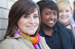 Multi-racial female college students. A group of female multi-racial college students outside against a brick wall royalty free stock images