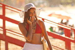 Multi-Racial Girl Makes Phone Call on Beach. Smiling mixed race girl in sun hat with smartphone while at Luquillo Beach Puerto Rico Royalty Free Stock Images