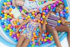 Multi Racial Girls Children Fun Playing in Colored Ball Pit. Interracial Group of girls, blond and African American children having fun laughing playing colorful Royalty Free Stock Photography