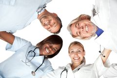Multi racial group or happy doctors smiling. Multi racial group or happy doctors looking down smiling at the camera - Isolated on white stock photography