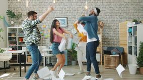 Multi-racial group of office workers dancing throwing documents laughing