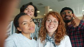 Multi-racial group of young people taking selfie in college library smiling