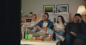 Multi-racial group of young people watching TV in dark apartment sitting on sofa. Multi-racial group of young people are watching TV in dark apartment sitting on stock video