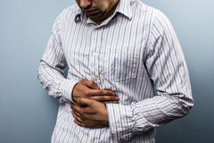 Multi racial man with constipation. Holding his stomach stock photos